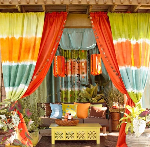 a colorful boho patio with bright curtains, pillows, lanterns, a neon coffee table and potted greenery