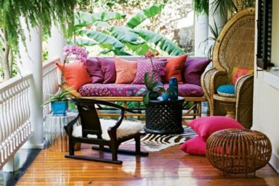 a colorful boho patio with a bright sofa and pillows, rattan chairs and an ottoman and potted blooms