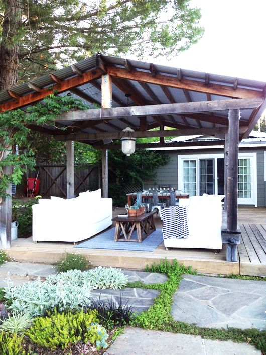 a rustic patio with white sofas, a dining space, printed textiles and a dark stained roof