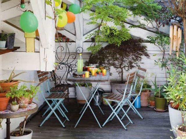 a bright boho patio with colorful balloons, potted greenery and a colorful chairs for dining