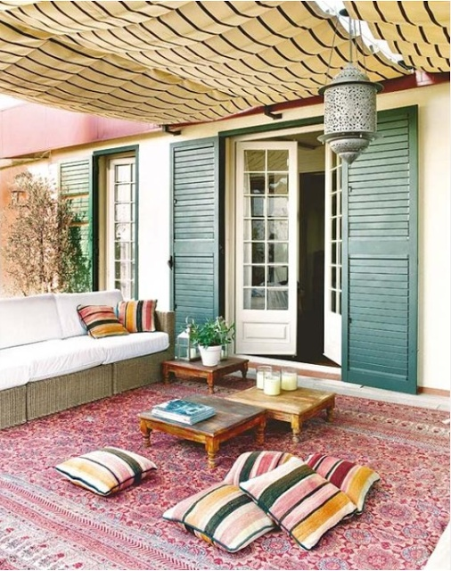 a simple and bright boho patio with striped pillows, low wooden tables, a Moroccan lantern