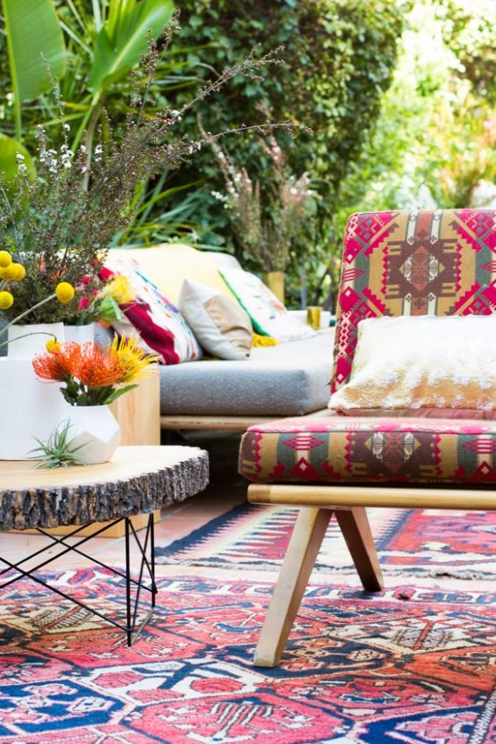 a bright boho patio with colorful rugs, furniture, pillows, a wooden slice coffee table and bright blooms