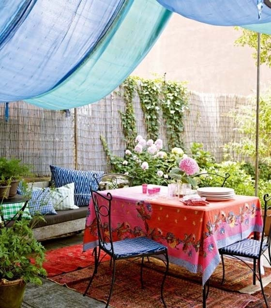 a colorful boho patio with a blue canopy, bright textiles and printed pillows, forged furniture