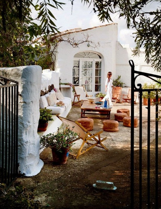 a boho patio in white with leather ottomans, folding furniture, potted greenery and blooms