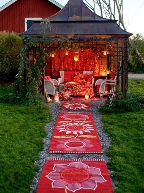 a super bold boho patio done in red and white, with white furniture and lots of red printed textiles