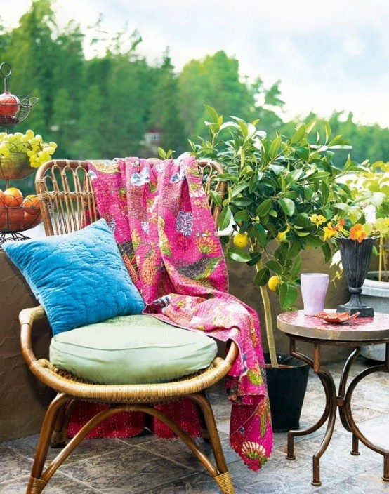 a colorful boho patio with rattan furniture, bright textiles, potted greenery and trees
