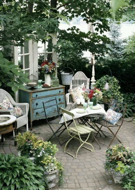 a relaxed patio in neutrals and pastels, with forged and wicker furniture and potted greenery and blooms