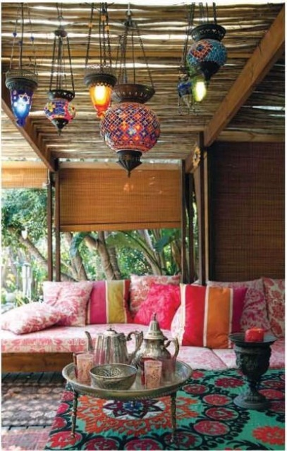 a bold Moroccan inspired patio with a colorful sofa and pillows, rugs and Moroccan-style lanterns