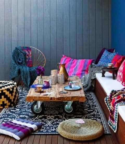 a super bright boho patio with a built-in bench, a rough wooden table on casters and super bright printed textiles, pillows and rugs