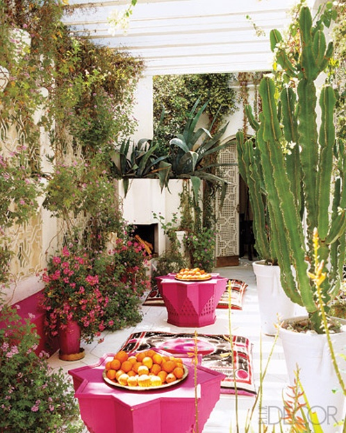 a bright boho patio with greenery and cacti, a bright rug, bright pink star-shaped coffee tables and bright blooms in pots