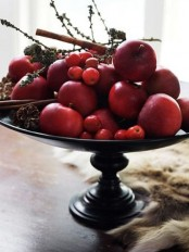 a natural fall centerpiece of a vintage bowl and red fruits and berries of all kinds