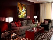 a statement burgundy wall and matching pillows and a coffee table for a bright living room look