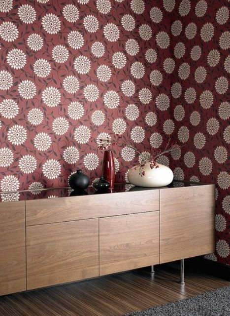 a wall done with retro inspired burgundy and gold printed wallpaper is a cool statement idea