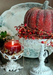 a burgundy candle and a pumpkin on a stand are simple and inexpensive touches to your interior