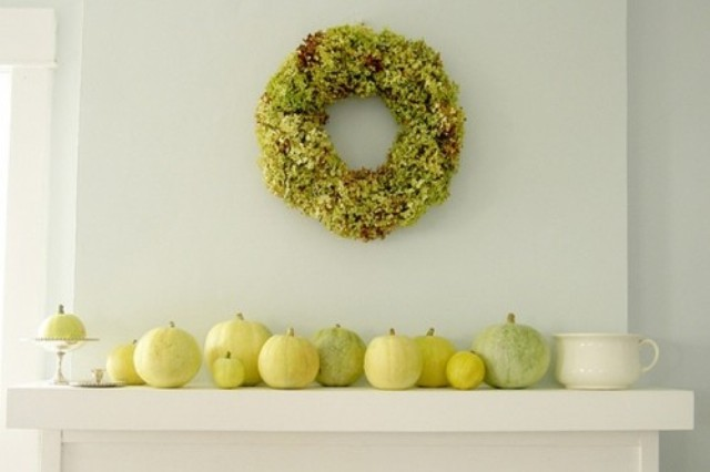 a modern rustic mantel decorated with a green hydrangeas wreath and natural white, green and yellow pumpkins