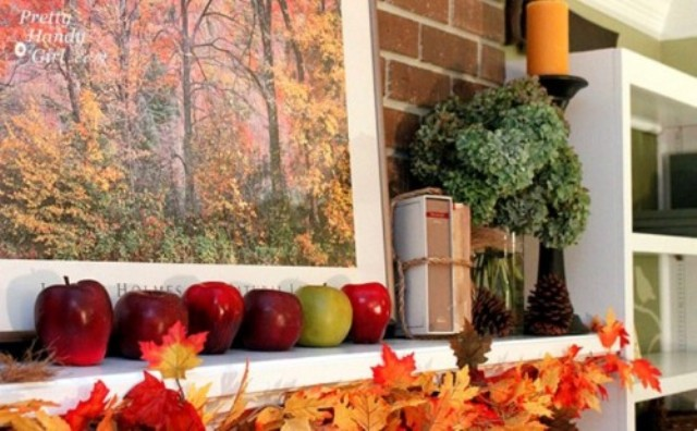 a simple fall mantel with a fall leaf garland, apples and an arrangement of green hydrangeas