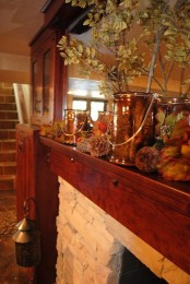 a rustic fall mantel decorated with pinecones, leaves and branches in a vase for a cozy feel