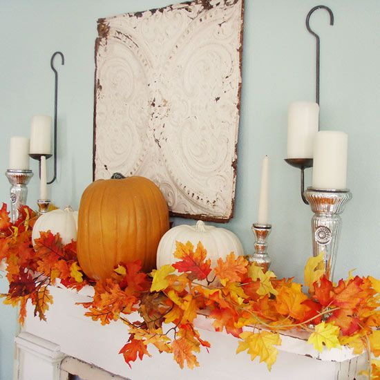 a chic fall mantel with bright fall leaves, orange and white pumpkins and candles in metallic candleholders