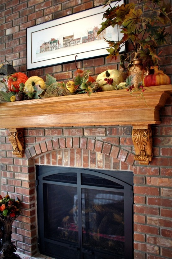 a lush fall mantel decorated with faux leaves, pumpkins, gourds, berries and other fall-related stuff