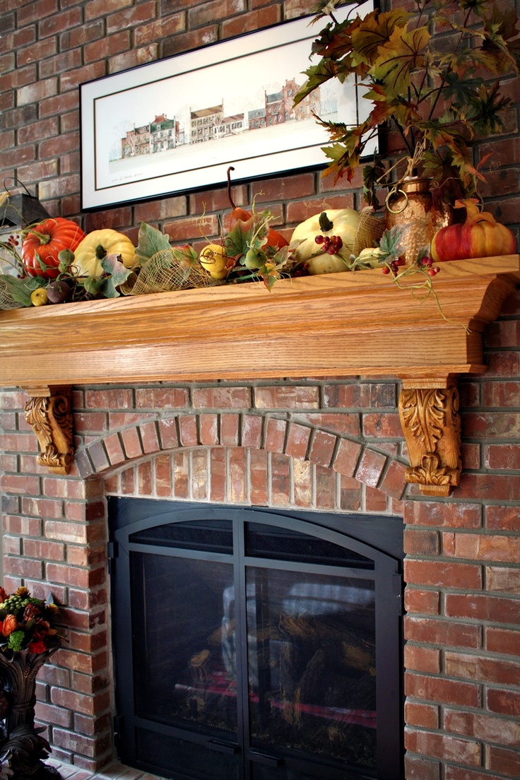 a lush fall mantel decorated with faux leaves, pumpkins, gourds, berries and other fall related stuff