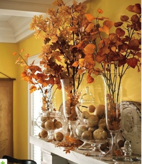 a rustic and modern fall mantel decorated with fall leaves in glass vases and pumpkins in large glass jars