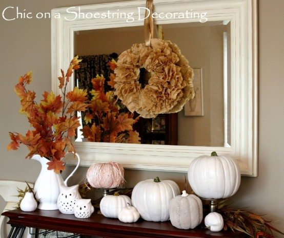 a vintage fall mantel decoarated with faux pumpkins in white, fall leaves, owls and a paper pompom wreath