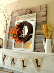 a rustic fall mantel with wheat, branches, a vine wreath with leaves and twigs, a burlap banner and a window