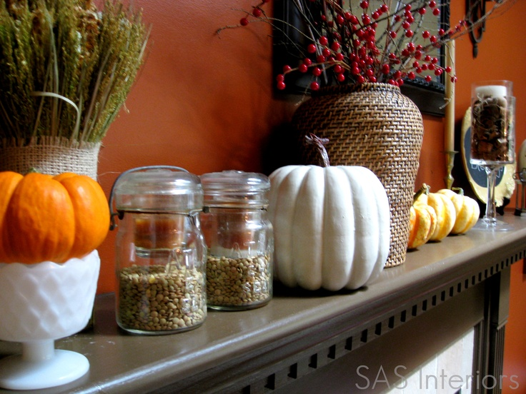 a cool fall mantel with faux pumpkins, grasses, berries and nuts in jars is a cool hint on the harvest time