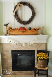 a fall mantel with a large vine wreath, a box with faux pumpkins, leaves, wheat and berries