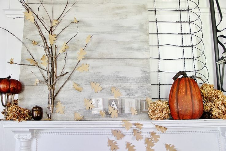 a cool fall mantel with some faux pumpkins, fake fall leaves, acorns, branches and dried hydrangeas
