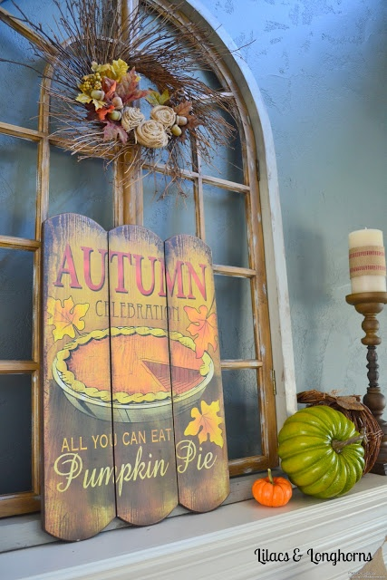 a vintage rustic fall mantel with a vintage sign, faux pumpkins, candles and a vinte wreath with twigs and fabric blooms