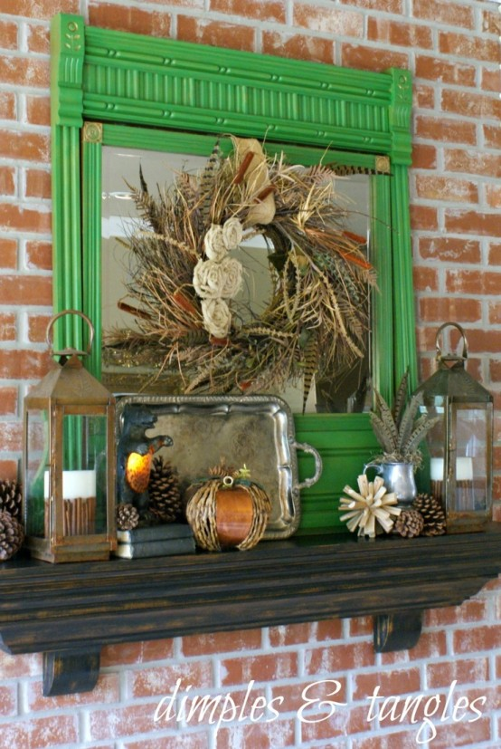 a quirky fall mantel with pinecones, pumpkins, candle lanterns, a mirror and feathers for a boho touch