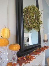simple fall mantel decor with a mirror with a greenery wreath, fall leaves and acorns, faux pumpkins and candles