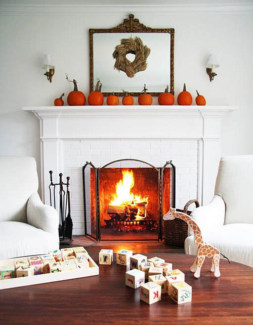 an elegant rustic mantel decorated with bright orange pumpkins, a wheat wreath hanging on a mirror
