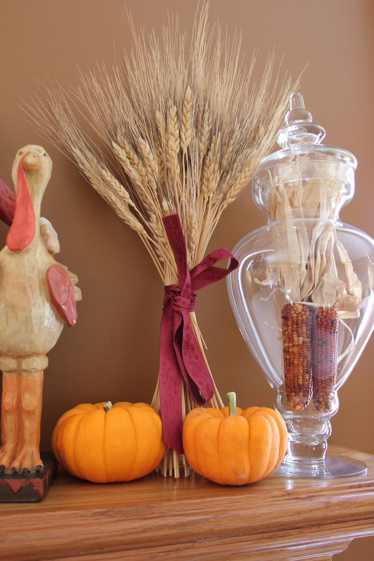 a colorful fall mantel with orange pumpkins, corn in a large glass jar, wheat and a fun chicken figurine