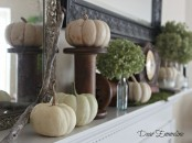 a vintage rustic mantel styled with white pumpkins, moss, green hydrangeas, metal stands