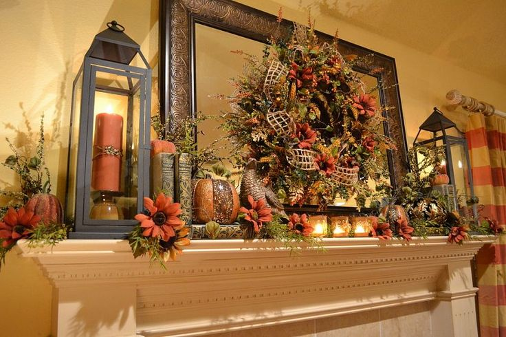 a lush rustic mantel in brown and rust, with faux blooms, leaves, books, candle lanterns and mesh