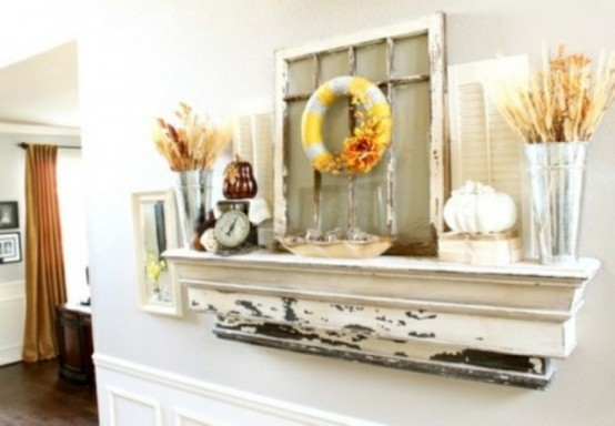 a rustic fall mantel decorated with wheat and leaves, faux pumpkins and a fabric wreath hanging on a vintage window frame