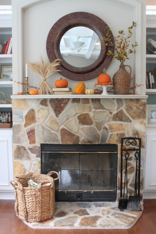 a chic fall mantel styled with wheat, berries, pumpkins and gourds, berry branches in a wicker vase plus a basket next to the fireplace
