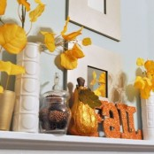a yellow and orange fall mantel with yellow fall leaves, pinecones in glass jars and a faux pumpkin and glitter letters