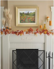 a simple fall mantel decorated with bright red fall leaves, wheat arrangements, candles in tall candle holders
