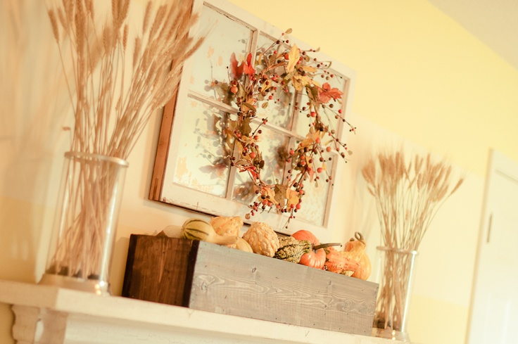 a rustic fall mantel with wheat arrangements, a faux leaf and berry wreath and a wooden box with faux pumpkins