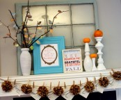 a shabby chic flal mantel with burlap pompoms, branches with bright fall leaves, signs and tiny pumpkins on stands