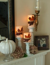 a simple fall mantel with a faux pumpkin, dried hydrangeas, candles with fall leaves attached in white candleholders