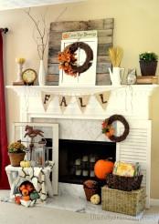 creative fall mantel decor with wheat, fall bloom arrangements, a burlap banner, faux pumpkins, a vine wreath and branches