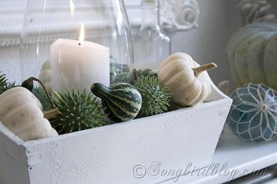 a neutral fall mantel with candles, a white wooden box and fresh pumpkins and gourds is a cute and beautiful fall decor idea