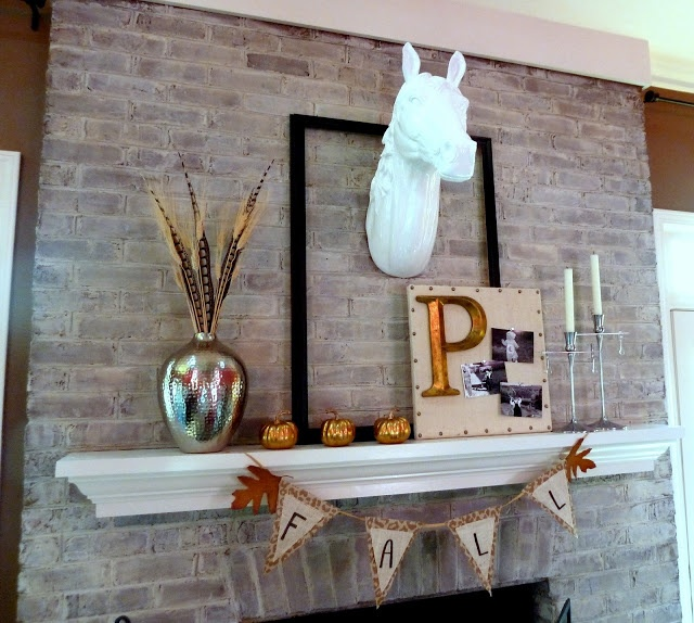 a fall mantel with a burlap banner, gilded pumpkins, a wheat arrangement, a sign and a faux animal head over it