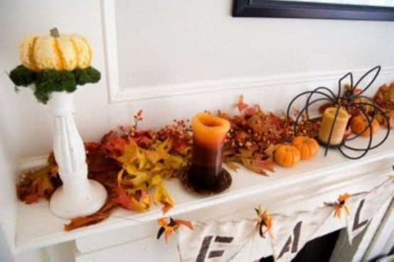 simple fall mantel decor with fake pumpkins, berries, candles in candleholders and a little pumpkin on a tall stand