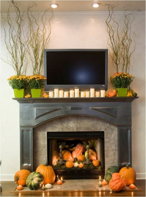 modern fall styling with bright fall blooms in planters, candles and fake pumpkins on the mantel and in the fireplace