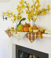 cozy rustic mantel styling with fall leaf branches in vases and real gourds and pumpkins on plaid napkins